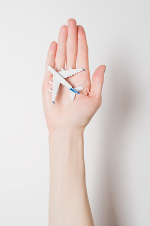 Airliner on the female palm on a light background. Concept of safe flights.