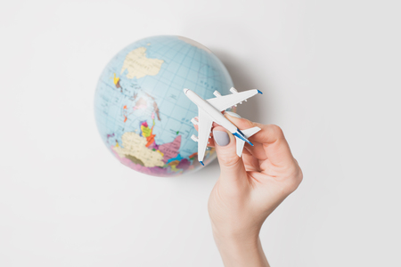 Passenger plane in a female hand on the background of the globe. Flight concept on a light background.