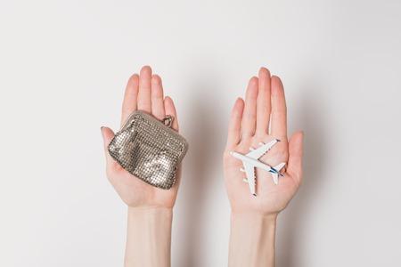 Passenger plane and wallet on female palms on a light background. Cheap flights. Standard-Bild