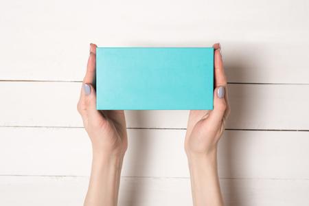 Rechthoekige turquoise doos in vrouwelijke handen. Bovenaanzicht. Witte tafel op de achtergrond