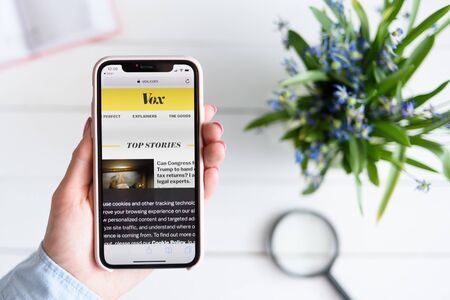 KHARKIV, UKRAINE - April 10, 2019: Apple iPhone X in female hand with vox.com site on the screen.