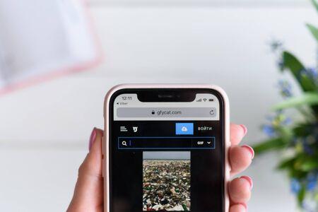 KHARKIV, UKRAINE - April 10, 2019: Woman holds Apple iPhone X with gfycat.com site on the screen. 報道画像