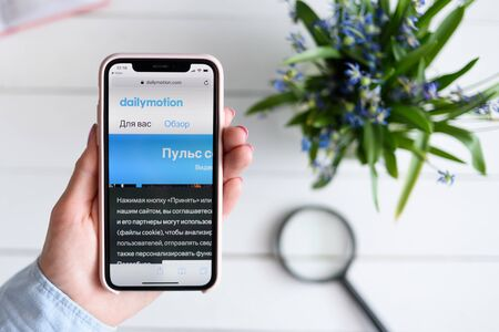 KHARKIV, UKRAINE - April 10, 2019: Apple iPhone X in female hand with dailymotion.com site on the screen.