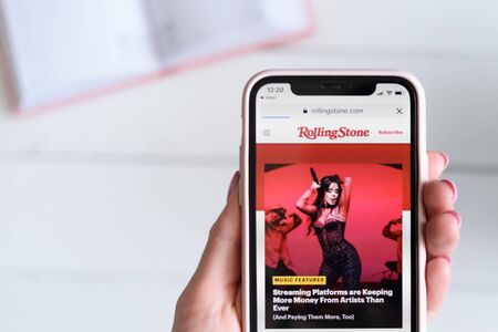 KHARKIV, UKRAINE - April 10, 2019: Apple iPhone X in female hand with rollingstone.com site on the screen. 報道画像