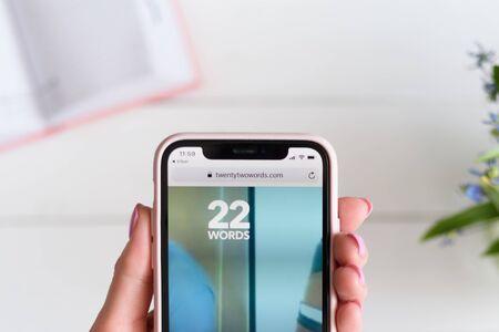 KHARKIV, UKRAINE - April 10, 2019: Woman holds Apple iPhone X with twentytwowords.com site on the screen. 報道画像