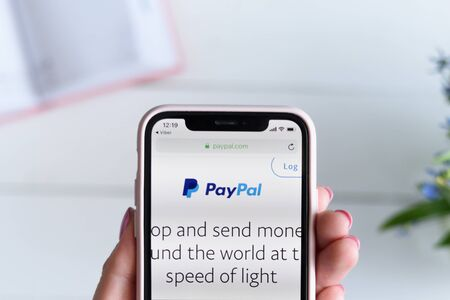 KHARKIV, UKRAINE - April 10, 2019: Apple iPhone X in female hand with paypal.com site on the screen.