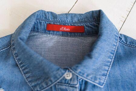 KHARKOV, UKRAINE - APRIL 27, 2019: Red label s.Oliver on blue denim shirt. Clothes concept. Details