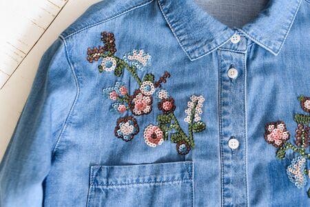 KHARKOV, UKRAINE - APRIL 27, 2019: Flowers embroidered with sequins on a blue denim shirt. Clothes concept. Details of shirt