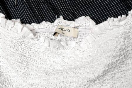 KHARKOV, UKRAINE - APRIL 27, 2019: White Papaya tag on white clothing. Close-up