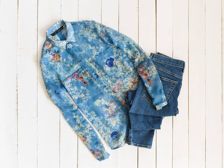 KHARKOV, UKRAINE - APRIL 27, 2019: Clothes fashion concept. Blue shirt and jeans on white wooden background. Top view 報道画像
