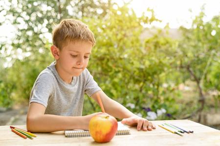 Cute boy draws with pencils still life. Open air. Garden in the background. Creative concept. Stockfoto