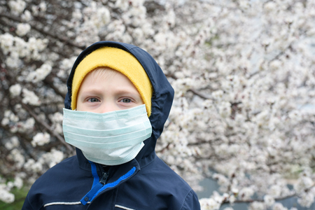 Boy in a medical protective mask outdoors. Flowering tree, spring day Stock Photo