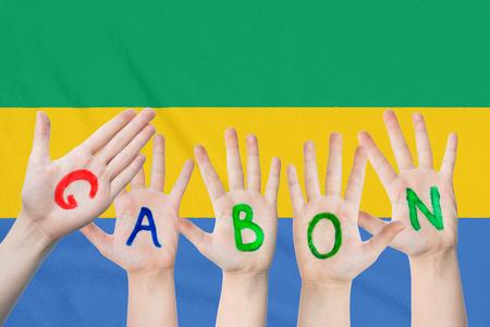 Inscription Gabon on the children's hands against the background of a waving flag of the Gabon Standard-Bild - 123448305