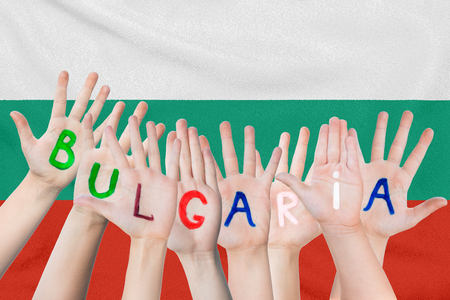 Inscription Bulgaria on the children's hands against the background of a waving flag of the Bulgaria Standard-Bild - 123448309