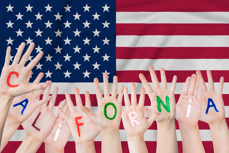 Inscription California on the children's hands against the background of a waving flag of the USA Standard-Bild - 123448455