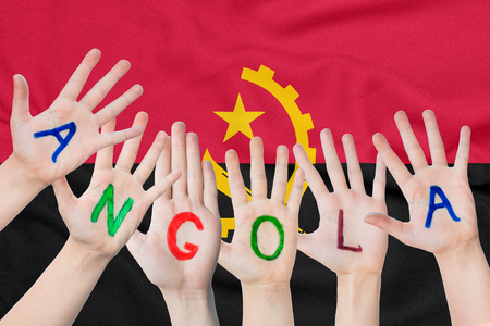 Inscription Angola on the children's hands against the background of a waving flag of the Angola Standard-Bild - 123448459