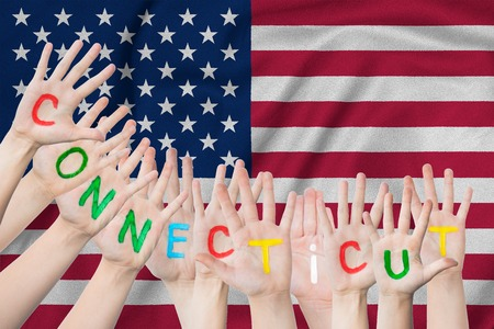 Inscription Connecticut on the children's hands against the background of a waving flag of the USA Standard-Bild - 123449883