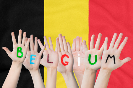 Inscription Belgium on the children's hands against the background of a waving flag of the Belgium Standard-Bild - 123449887