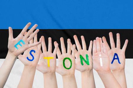Inscription Estonia on the children's hands against the background of a waving flag of the Estonia Standard-Bild - 123450222