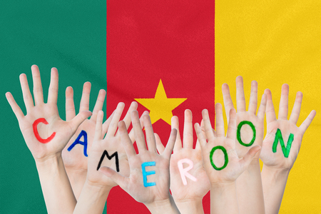 Inscription Cameroon on the children's hands against the background of a waving flag of the Cameroon Standard-Bild - 123450348