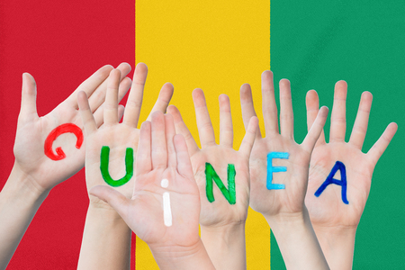 Inscription Guinea on the children's hands against the background of a waving flag of the Guinea Standard-Bild - 124540114
