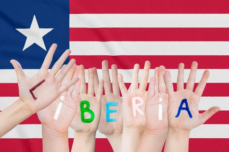 Inscription Liberia on the children's hands against the background of a waving flag of the Liberia Standard-Bild - 124623421