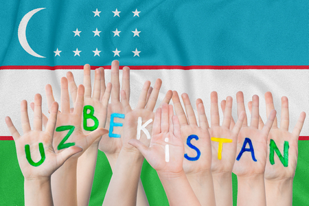 Inscription Uzbekistan on the children's hands against the background of a waving flag of the Uzbekistan Standard-Bild - 124623424