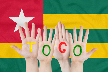 Inscription Togo on the childrens hands against the background of a waving flag of the Togo