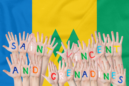 Inscription Saint Vincent and the Grenadines on the childrens hands against the background of a waving flag of the Saint Vincent and the Grenadines