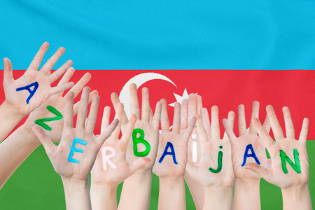 Inscription Azerbaijan on the children's hands against the background of a waving flag of the Azerbaijan Standard-Bild - 124623524