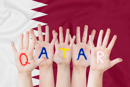 Inscription Qatar on the children's hands against the background of a waving flag of the Qatar Standard-Bild - 123933237