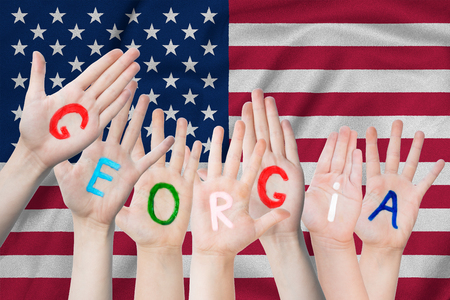 Inscription Georgia on the children's hands against the background of a waving flag of the USA Standard-Bild - 124372735