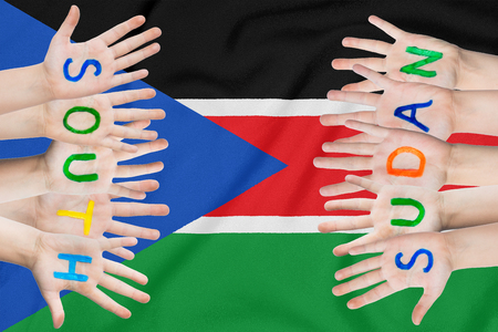 Inscription South Sudan on the children's hands against the background of a waving flag of the South Sudan Standard-Bild - 124372745