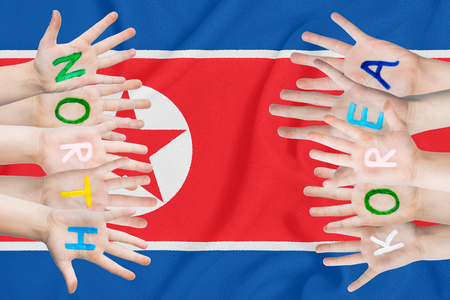 Inscription North Korea on the children's hands against the background of a waving flag of the North Korea Standard-Bild - 124372747