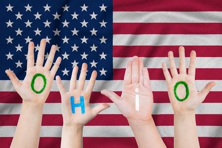 Inscription Ohio on the children's hands against the background of a waving flag of the USA Standard-Bild - 124372751