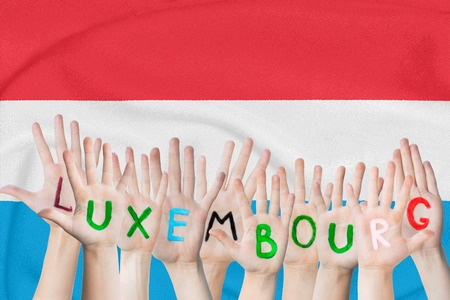 Inscription Luxembourg on the children's hands against the background of a waving flag of the Luxembourg Standard-Bild - 124623526