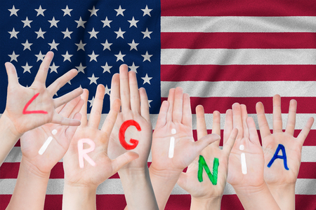 Inscription Virgia on the childrens hands against the background of a waving flag of the USA Stock Photo