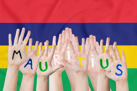 Inscription Maur4itius on the children's hands against the background of a waving flag of the Mauritius Standard-Bild - 124626823