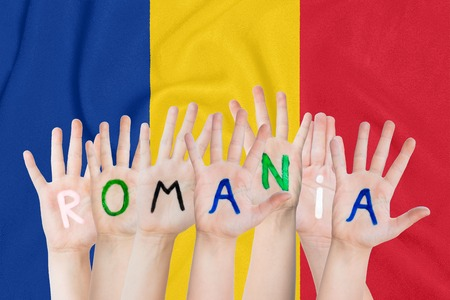 Inscription Romania on the children's hands against the background of a waving flag of the Romania Standard-Bild - 123933373