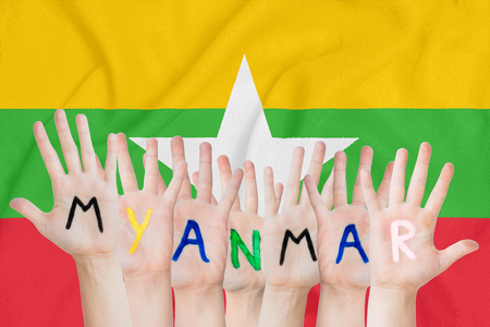Inscription Myanmar on the children's hands against the background of a waving flag of the Myanmar Standard-Bild - 123933374