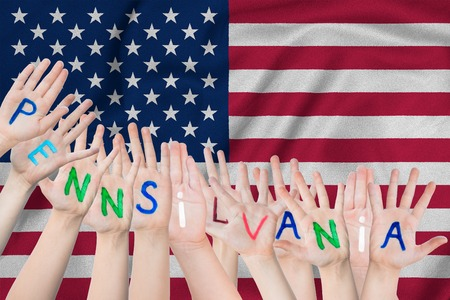 Inscription Pennsilvania on the children's hands against the background of a waving flag of the USA Standard-Bild - 123933380