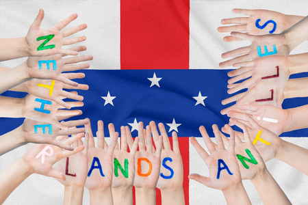 Inscription Netherlands Antilles on the children's hands against the background of a waving flag of the Netherlands Antilles Standard-Bild - 123933384