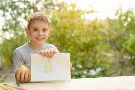 Cute boy shows drawn pear. Open air. Garden in the background. Creative concept. 免版税图像