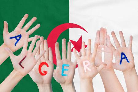 Inscription Algeria on the children's hands against the background of a waving flag of the Algeria Standard-Bild - 124540153