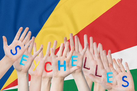 Inscription Seychelles on the children's hands against the background of a waving flag of the Seychelles Standard-Bild - 124540155