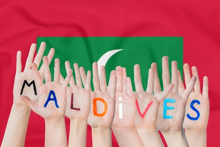 Inscription Maldives on the children's hands against the background of a waving flag of the Maldives Standard-Bild - 124540157