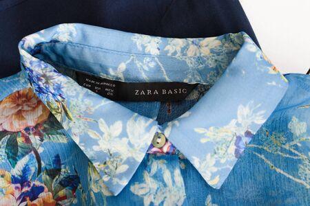 KHARKOV, UKRAINE - APRIL 27, 2019: Black label ZARA BASIC and collar of blue floral blouse. Clothes concept. Details