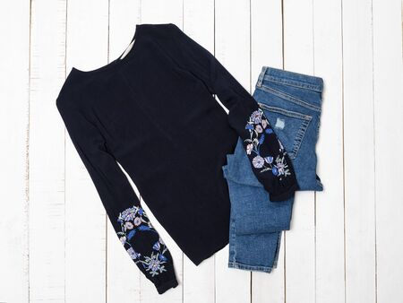 KHARKOV, UKRAINE - APRIL 27, 2019: Clothes fashion concept. Blue shirt with embroidery and jeans on wooden background.