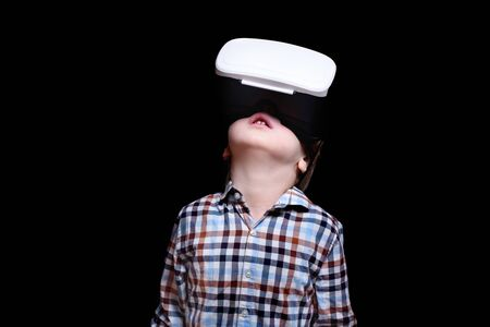 Little blond boy with glasses of virtual reality looks up. Plaid shirt. Black background