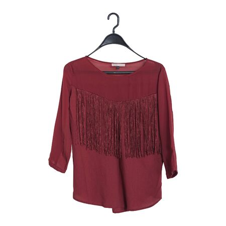 Bordeaux blouse with fringe hanging on a hanger. Isolate. White background.